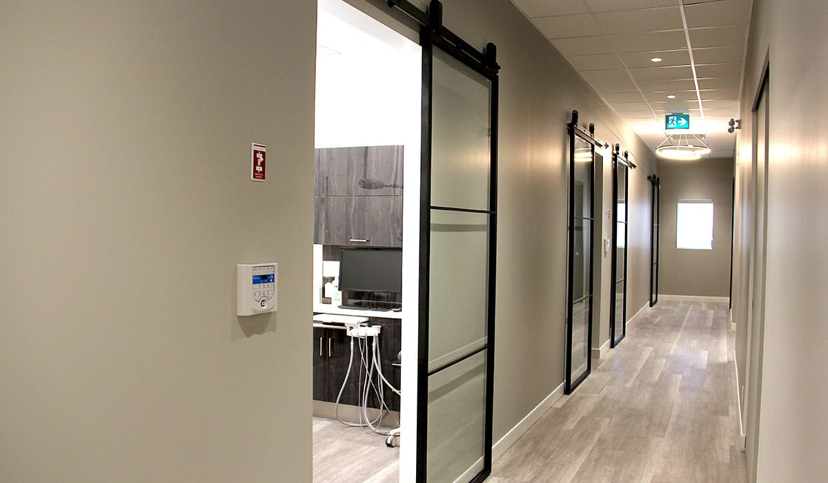 offwhite hallway in dental practice with glass doors for exam rooms