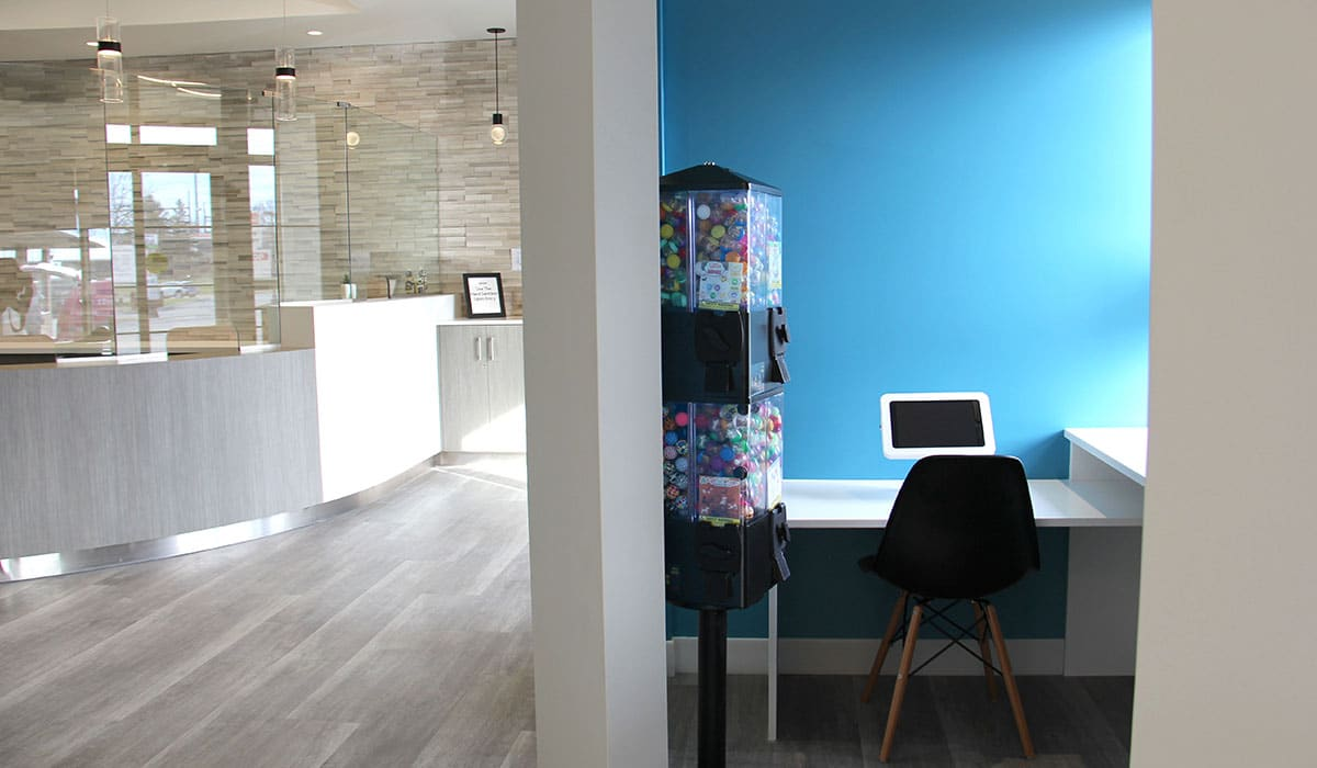 dental office reception area with grey floors and black chairs