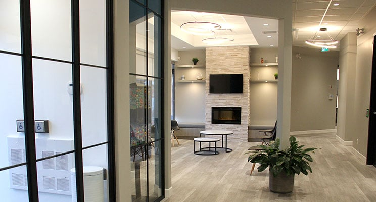 dental office waiting room with grey floors, fireplace and flat screen TV